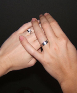Two white women's hands with rings on them touching tenderly