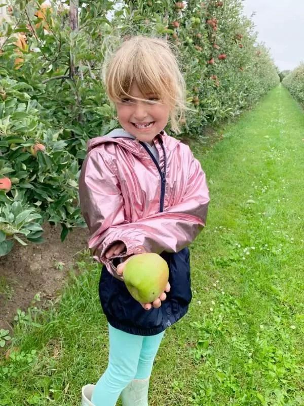 Miya houd een appel in haar hadn op de boomgaard van Servero