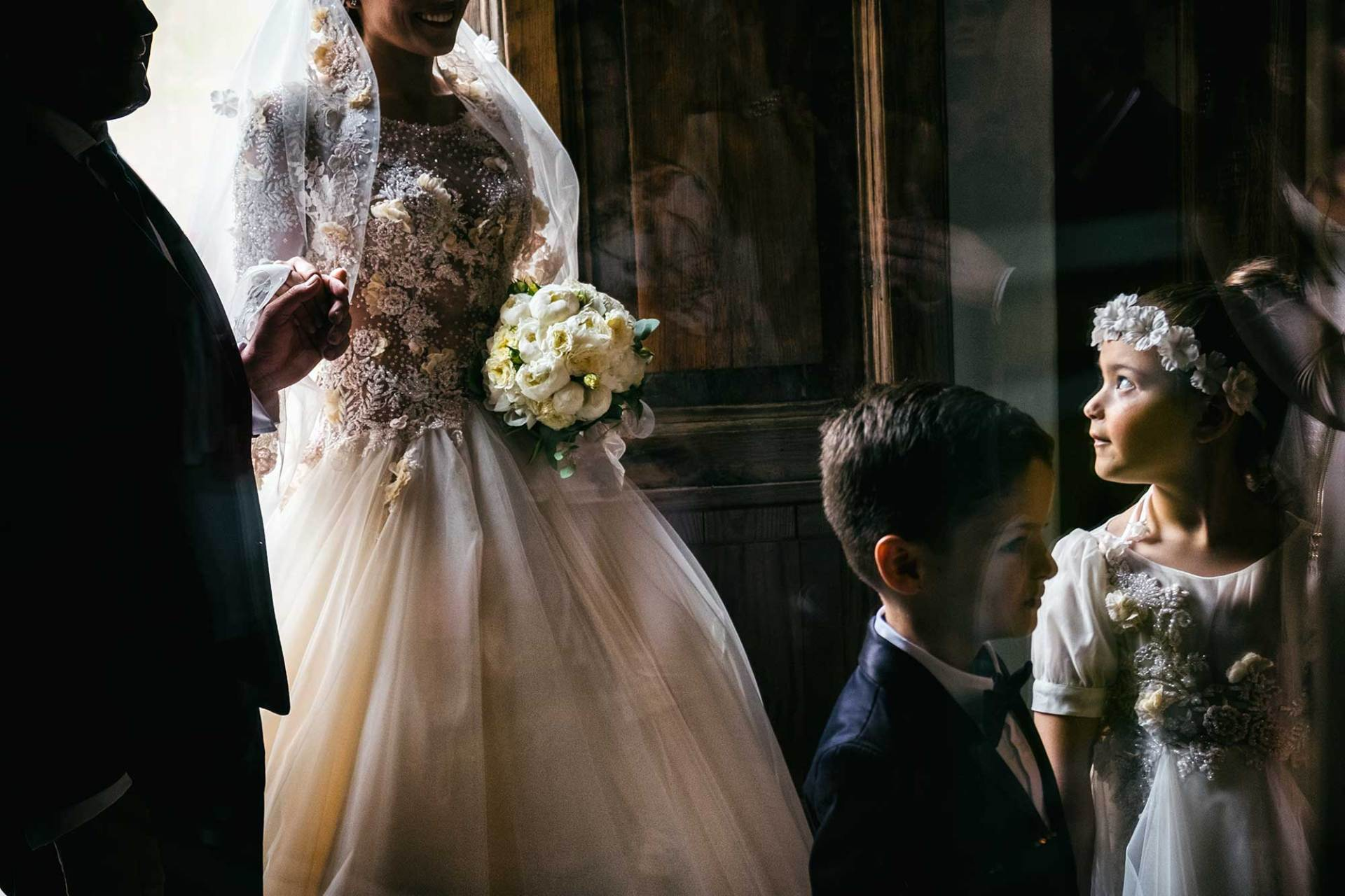 la fotografia per matrimonio che ritrae una sposa mentre entra in chiesa accompagnata dal papà
