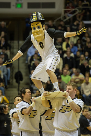 Purdue Pete surfs across the Mackey Arena floor on a commemorative surfboard from the Maui Invatational