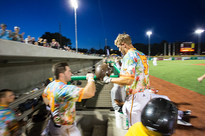 Chris Klenk is congratulated after scoring the tying run for the Kokomo Jackrabbits