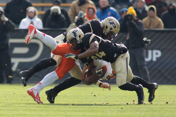Wil Lucas (45) and Frankie Williams (24) of Purdue tackle Illini running back Josh Ferguson (6)