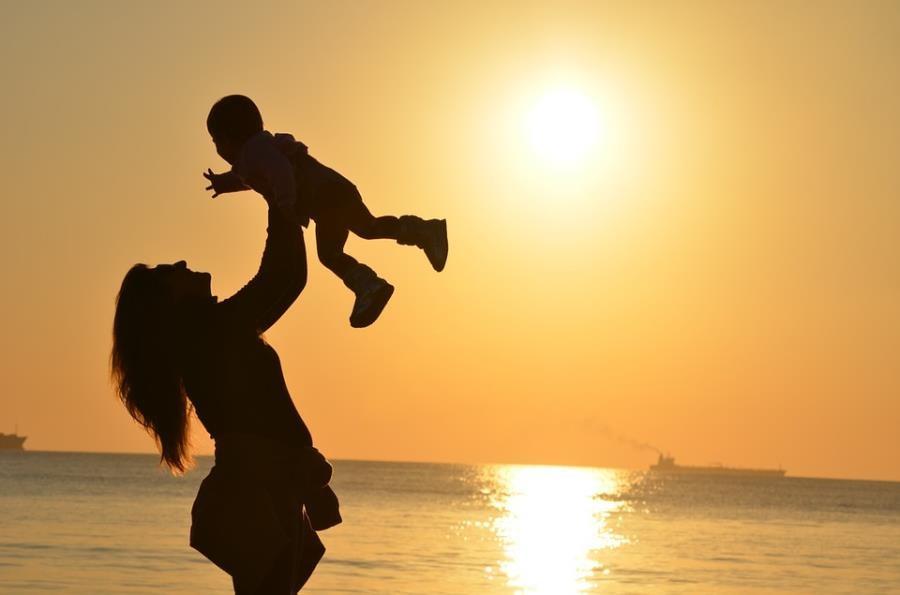 Matka podnosząca do góry dziecko na tle zachodzącego słońca nad morzem