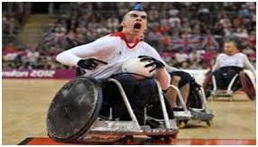 Ubrany w białą koszulkę i czarne spodnie człowiek siedzi na wózku inwalidzkim. W lewej ręce trzyma piłkę do rugby. Za nim  widać jeszcze dwóch sportowców na wózkach inwalidzkich a  w oddali widać publiczność zgromadzoną w hali sportowej