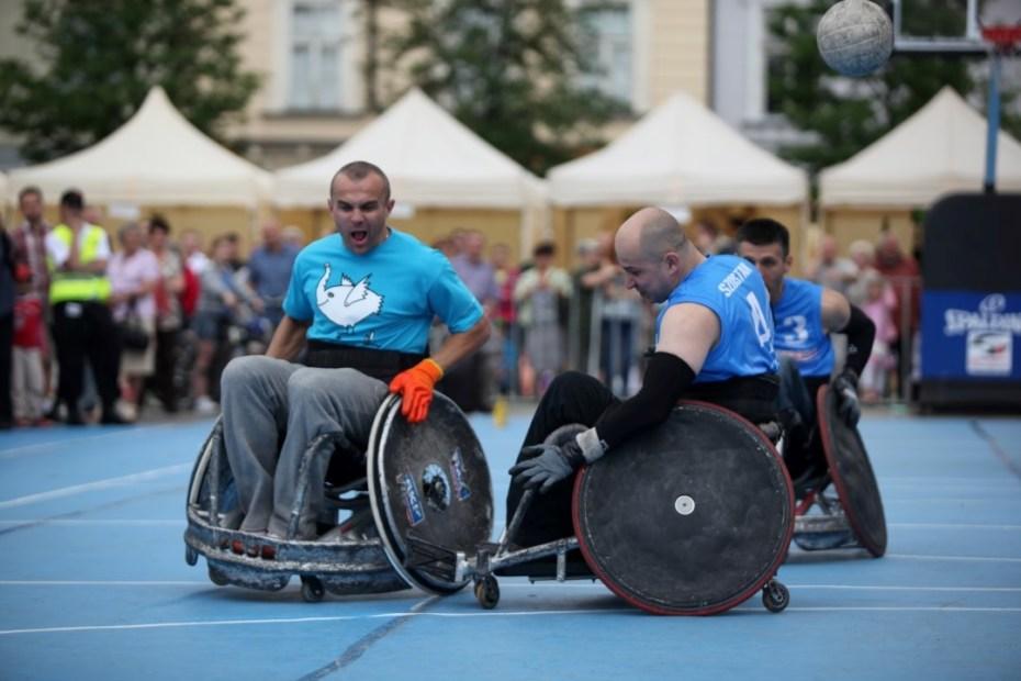 Na tle tłumu ludzi trzech sportowców na wózkach inwalidzkich gra w koszykówkę