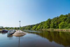 rzeka, po prawej stronie las na drugim brzegu rzeki, po lewej stronie łódź