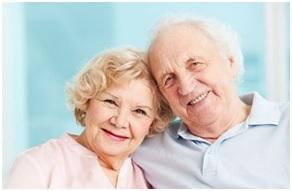 Na zdjęciu dwóch seniorów - kobieta i mężczyzna. Seniorka opiera głowę na ramieniu seniora
