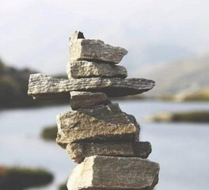 Kilka kamieni ułożonych jeden na drugim w tle rzeka i przyroda