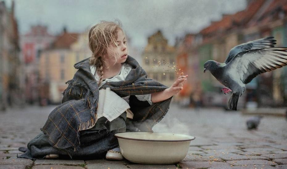 Mała dziewczynka z zespołem Downa owinięta w koc na tle kamienic poznańskiego starego rynku obok niej miska i podlatujący do niej gołąb