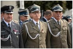Trzech starszych żołnierzy stojących na baczność. Są ubrani w mundury