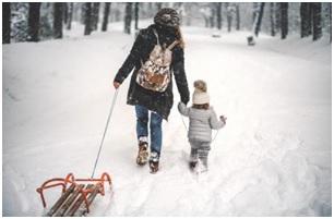 Zimowy krajobraz - kobieta ciągnie sanki. Obok niej w śniegu kroczy dziecko