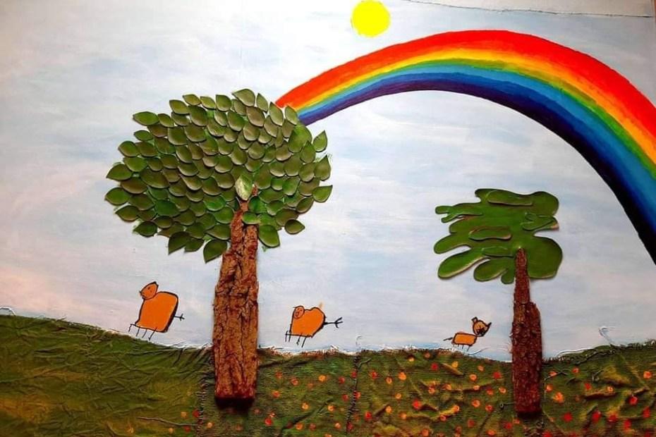 Obraz przedstawiający dwa drzewa, trzy owce i sięgającą za horyzont tęczę