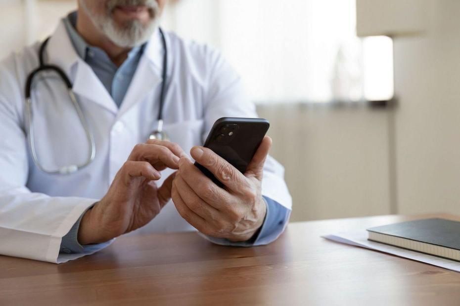 Na zdjęciu lekarz z telefonem w ręku