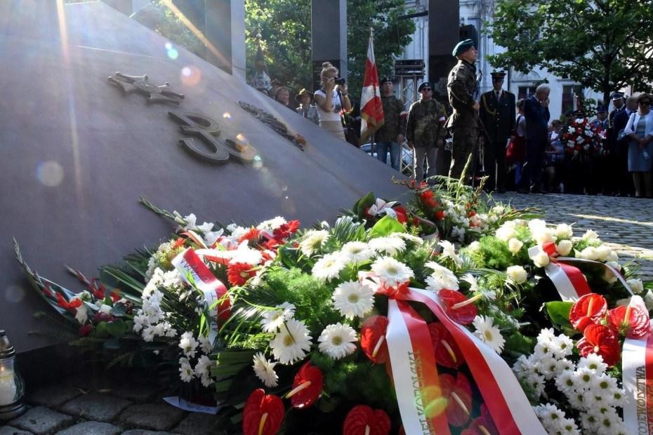 Na zdjęciu Pomnik Polskiego Państwa Podziemnego i Armii Krajowej w Poznaniu. Na nim złożony wieniec kwiatów. Zgromadzeni ludzie na drugim planie