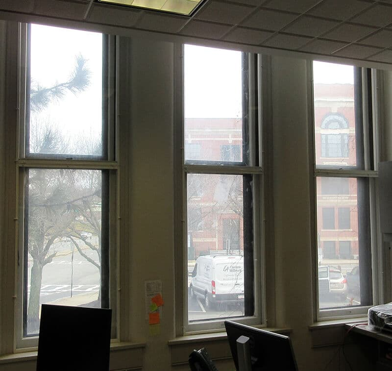 Keeping an office space warm and toasty with discreet interior storm windows while maintaining the gorgeous wavy glass windows.