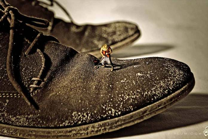 Man cleaning shoes. Surreal photography.
