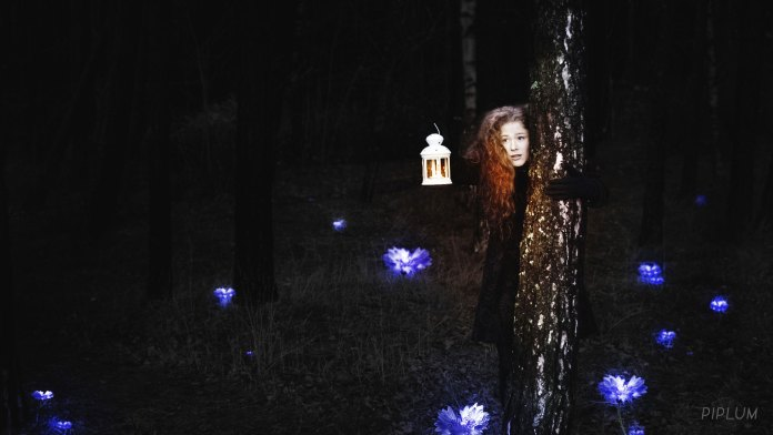 Redhead girl in lost in city palanga. Hidding behind the tree. Shinning blue flowers around.