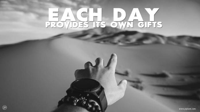 Each-day-provides-its-own-gifts-inspirational-quote-mans-hand-desert-sand