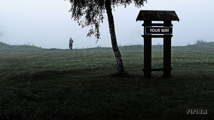 Inspirational Life Quote. Man walking in a fog and road sign says: your way.