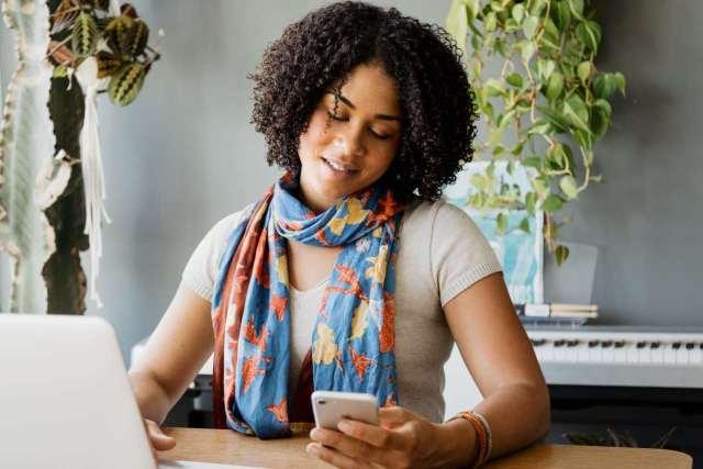 Uma foto de uma mulher segurando e olhando um celular