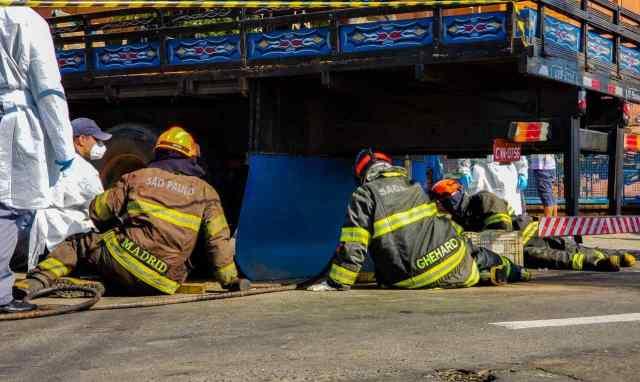 Na imagem bombeiros trabalham para remover o corpo