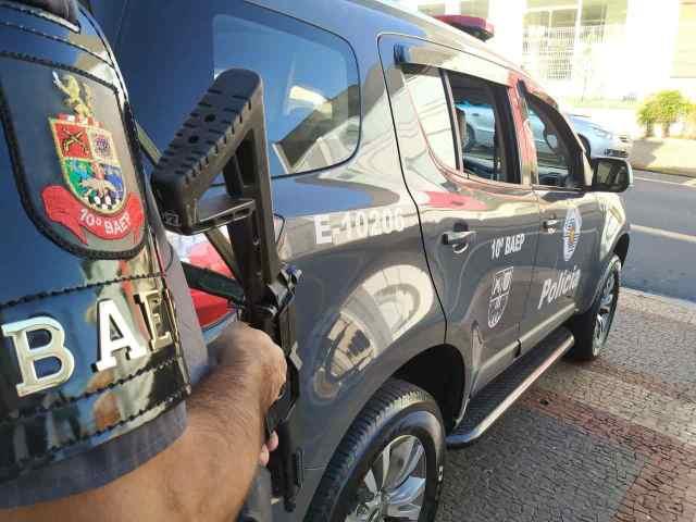 Na imagem temos um policial do BAEP armado ao lado da viatura E-10206