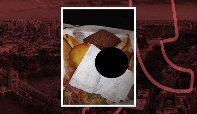 Na imagem podemos ver uma caixa cheia de salgados. Há um circulo preto tampando o pedaço do dedo encontrado