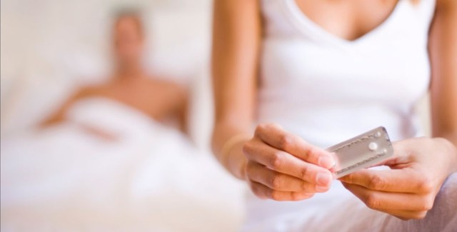 Uma foto de uma mulher segurando uma cartela de pílula do dia seguinte