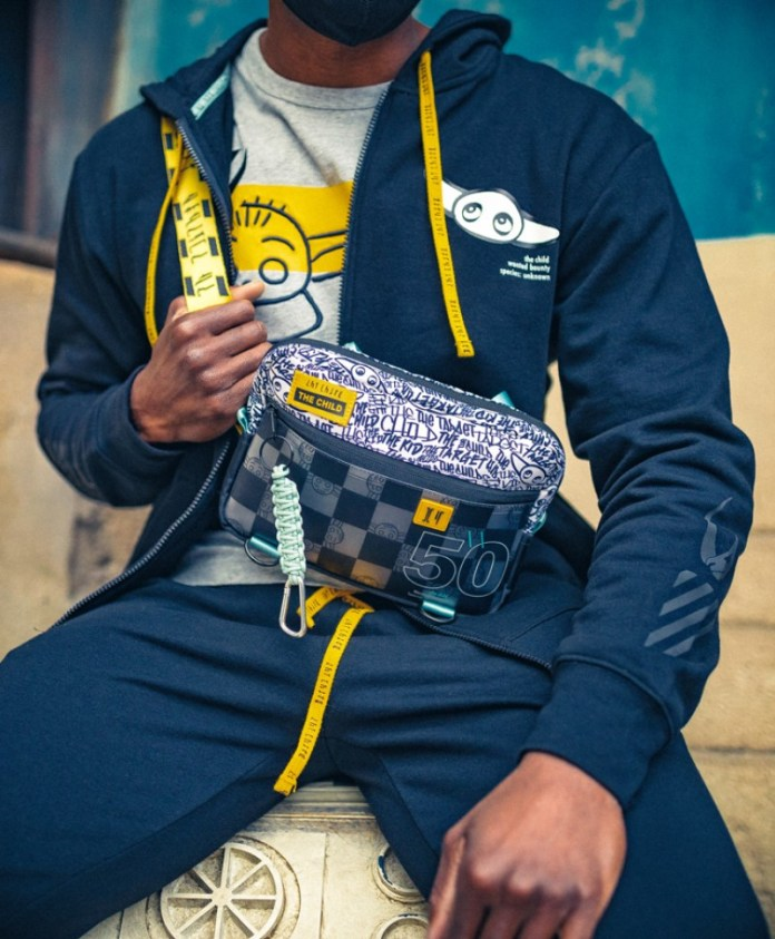 Blue zip front hoodie with blue pants. Baby Grogu on the sweatshirt and a white shirt with Baby Grodu printed on it underneath. Crossbody Bag with graffiti type designs