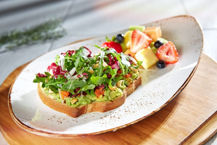 Toast with avocado and salad on top and chopped fruit