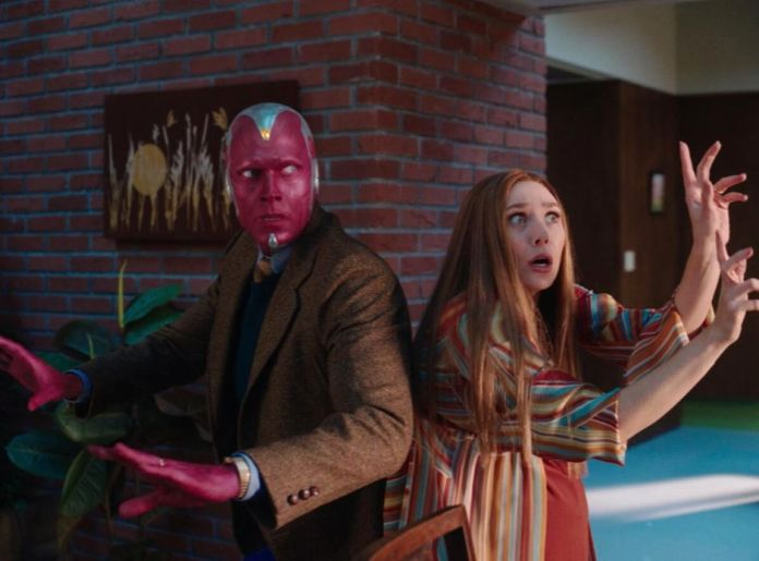 Vision and Wanda in 70's attire standing back to back ready to fight