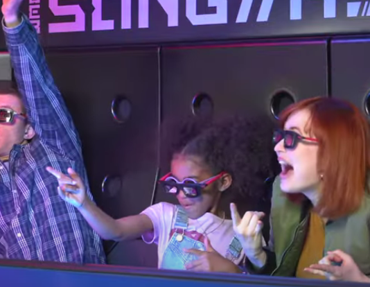 Tom Holland, a child and a woman all enjoy the new attraction with their 3D goggles