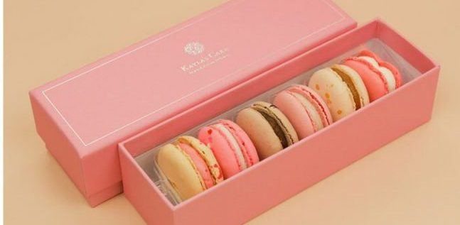 Pink rectangular box with Kayla's Cakes written in white. Inside are 6 macarons in various shades of pink, white, cream and brown