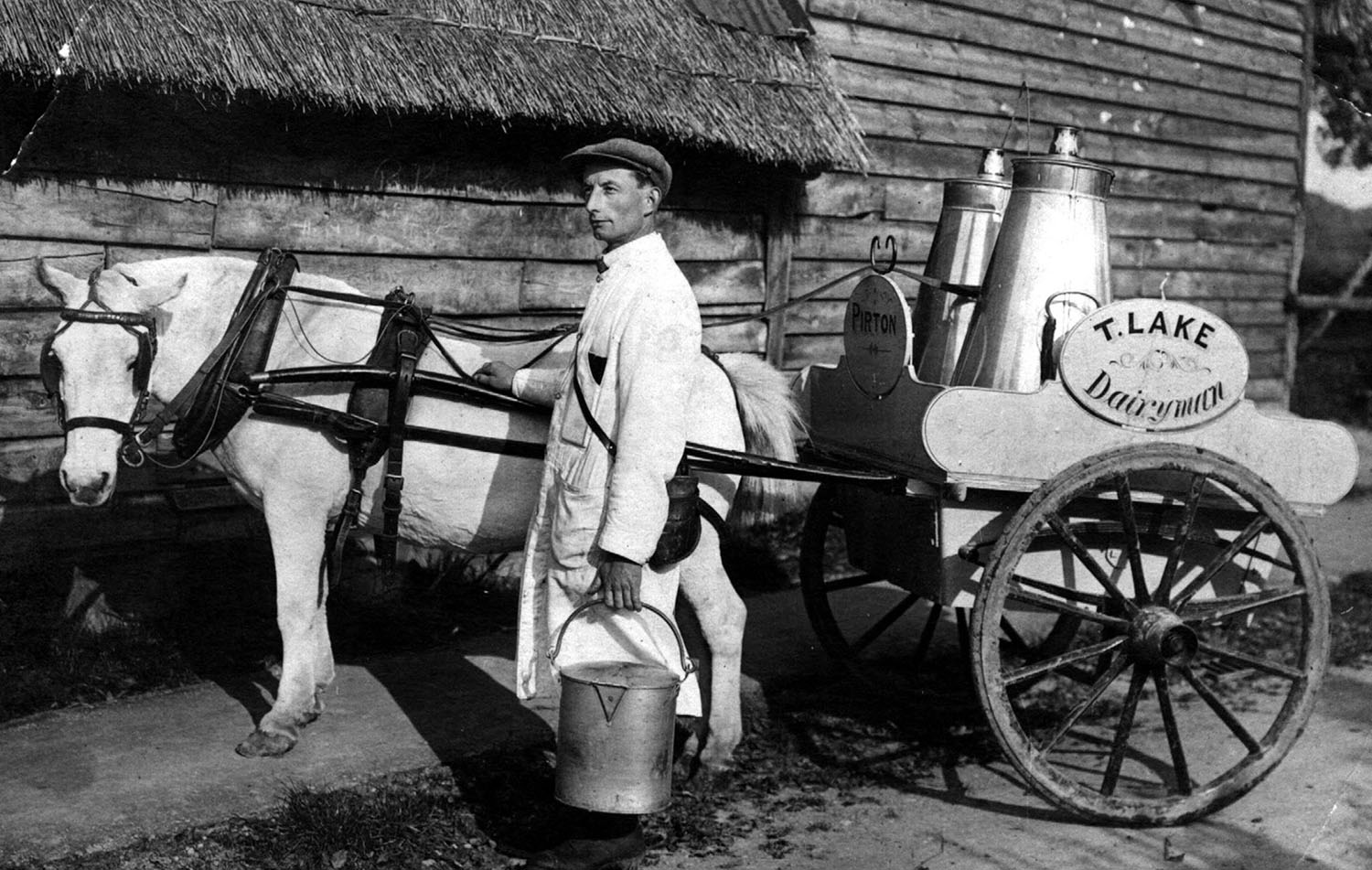 "1926 Tom Lake, Pirton's first milkman, with his churns, pails and measuring jugs. He delivered milk twice a day as there were no fridges to keep milk cool. Milk was ""straight from the cow"" and was not pasteurised as is now required by health legislation."