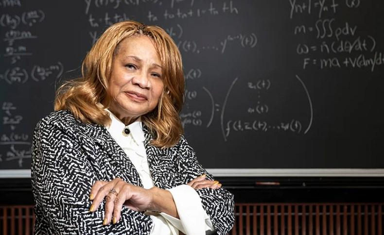 Elayne Arrington stands in front of a blackboard with math equations in white chalk