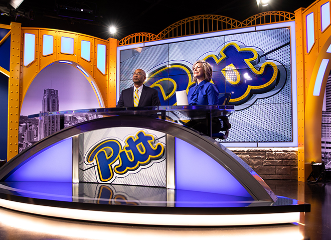 two people at a news anchor desk with Pitt script