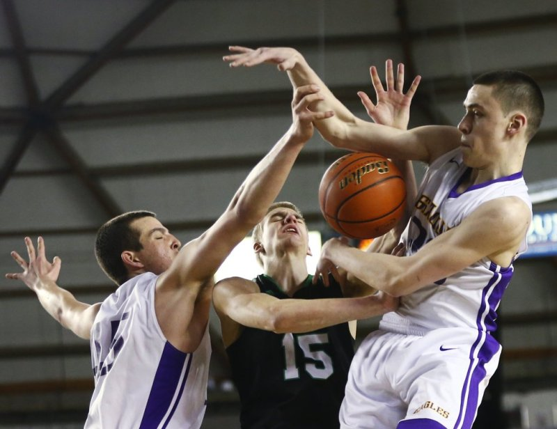Kentwood's Beau Roggenbach, center, draws a foul off of Issaquah defense, including Dominic Postle, left and Ethan Hammond during the Hardwood Classic quarterfinals at the Tacoma Dome on Thursday, March 3, 2016. The Hardwood Classic continues through Saturday. Kentwood pulled ahead at the end to win a close game against Issaquah, 57-51.