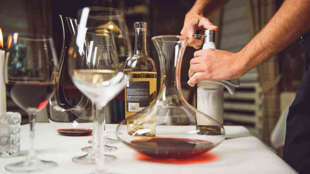 Waiter is opening bottle with white wine. Photo by YakobchukOlena/iStock