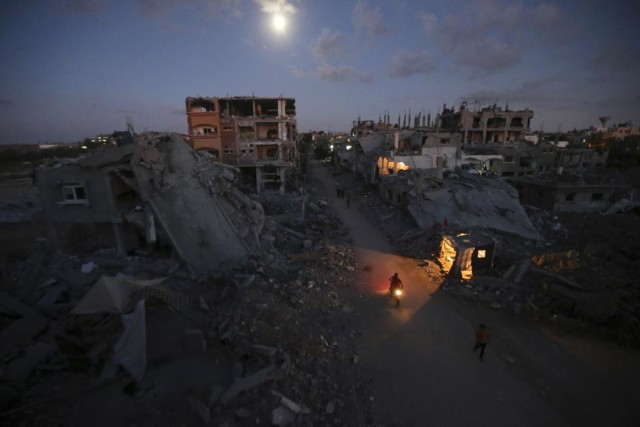 Palestinians commute along a road between ruins of houses, which witnesses said were damaged or destroyed during the Israeli offensive, in Beit Hanoun