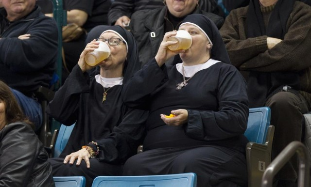 Two women wearing nun outfits drink beer at the 2014 Tim Hortons Brier curling championships in Kamloops