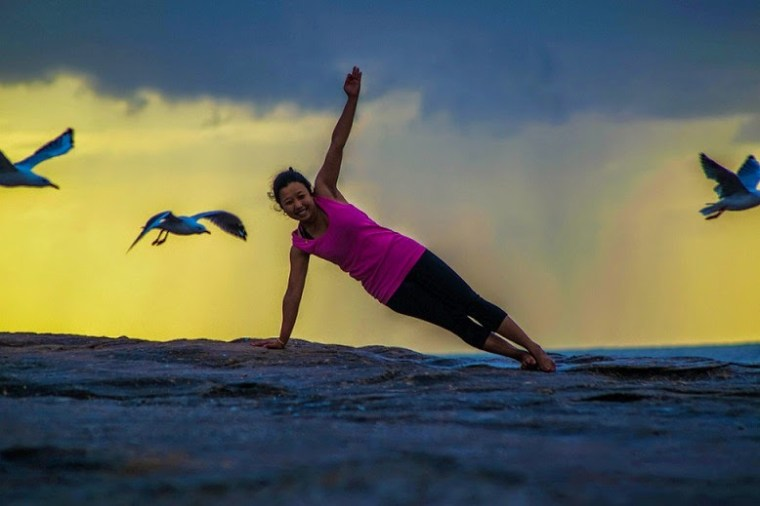 girl doing side planks on a cliff