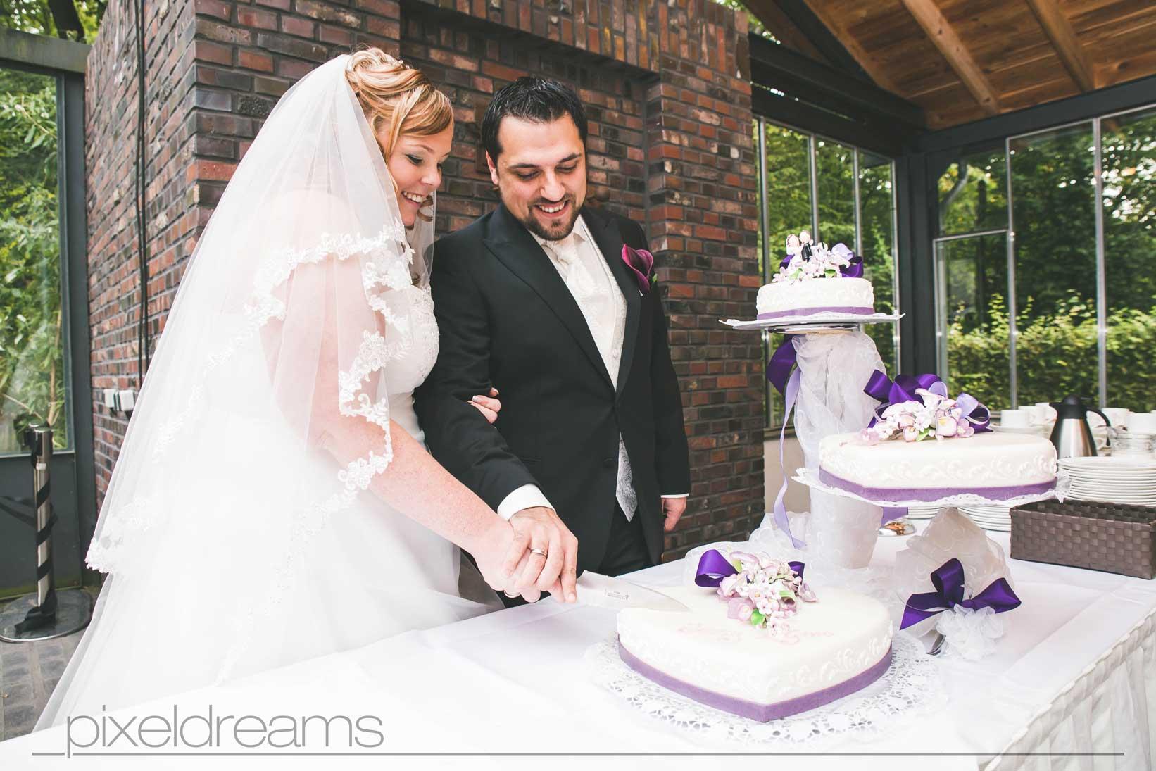 braut und bräutigam schneiden hochzeitstorte bei ihrer hochzeitsfeier
