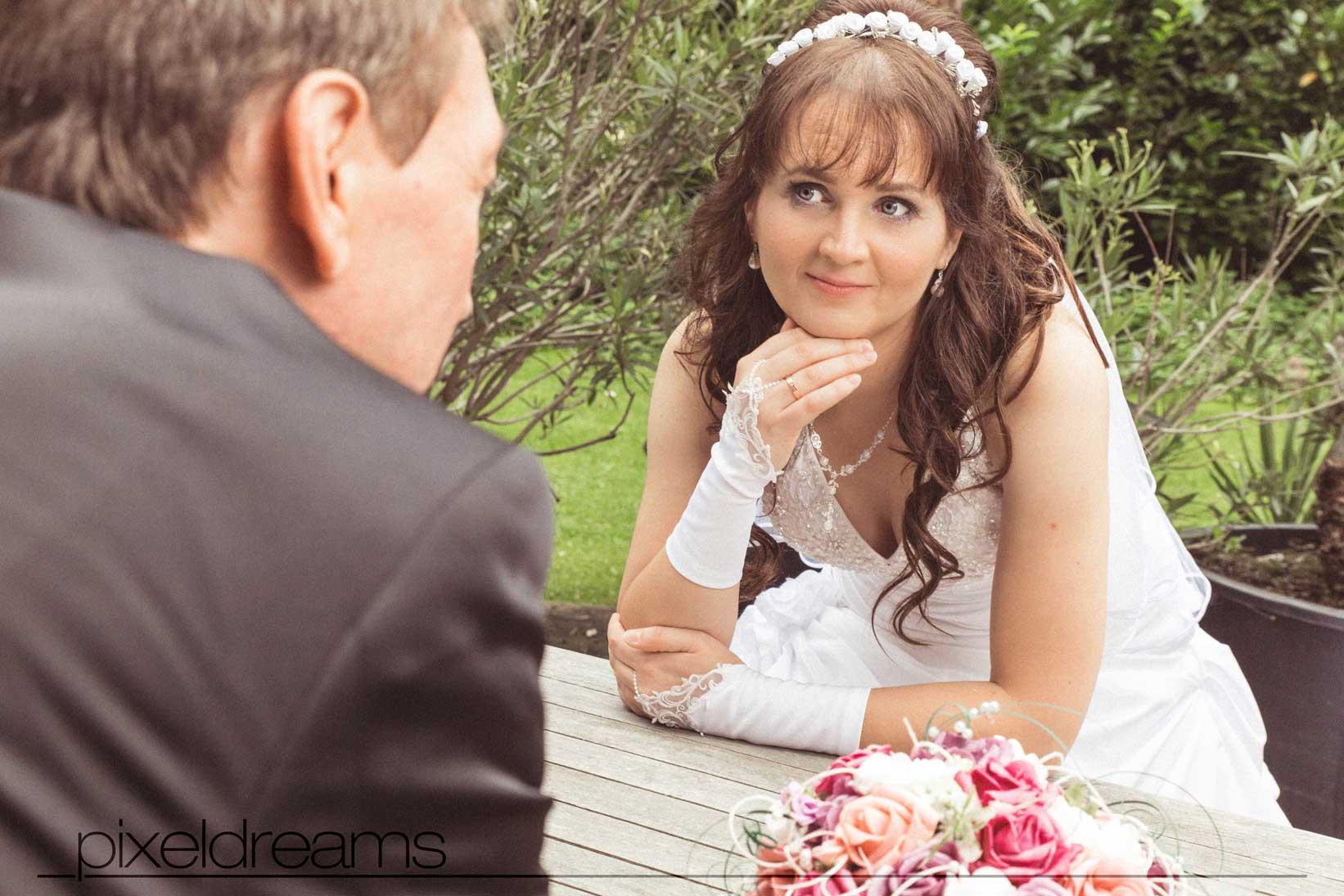 das brautpaar posiert an einem tisch während der Hochzeitsfotograf ihn schräg von hinten und sie schräg von vorne fotografiert
