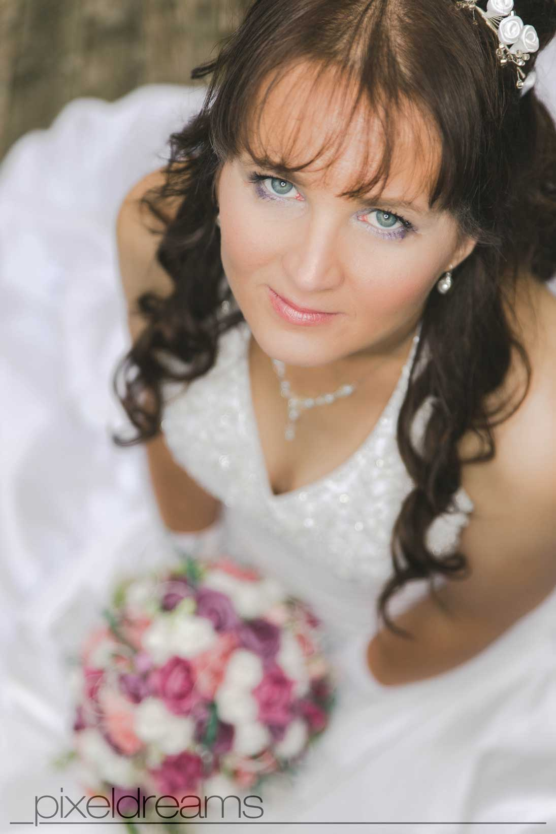 Braut mit Brautstrauß in pose. Der Hochzeitsfotograf nimmt eine erhöhte Vogelperspektive ein. Das Brautmakeup kommt hier gut zur Geltung.