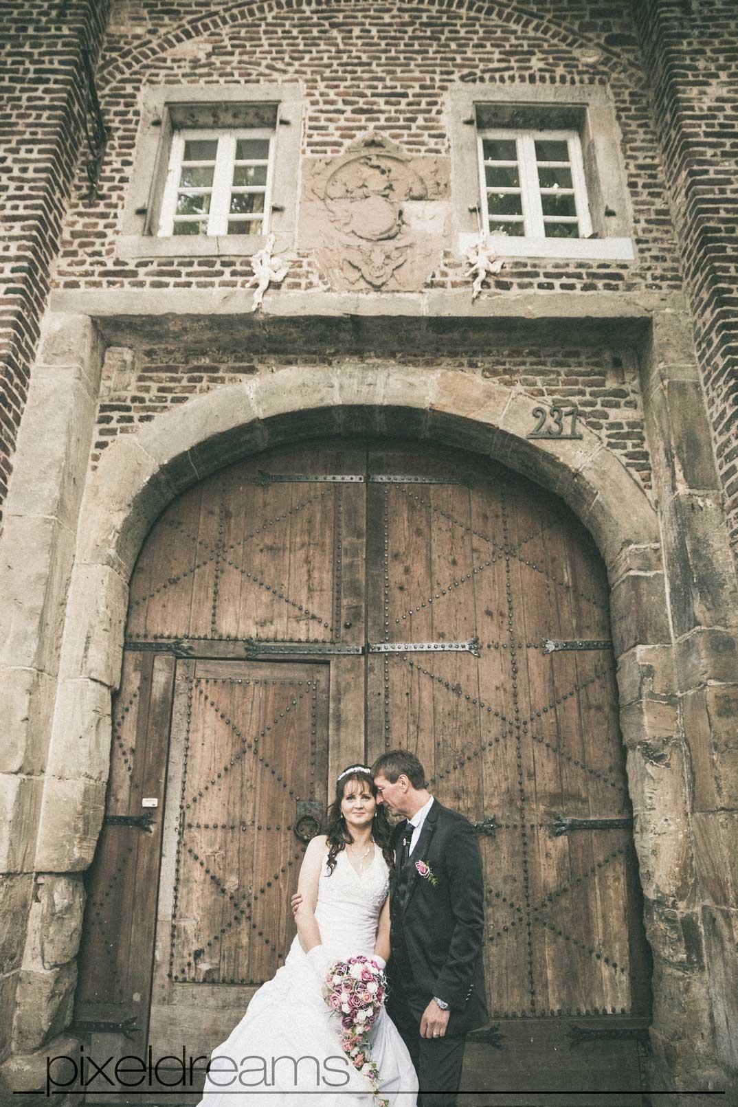 Hochzeitsfotografie vor dem Gutshof der Kommandeursburg in Kerpen Blatzheim. Braut und Bräutigam schmusen.