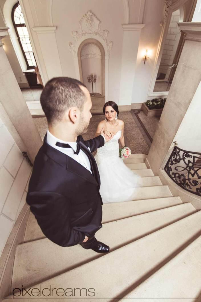 braut und bräutigam gehen die treppen hoch im schloss dyck während sie ihres brautstrauß hält