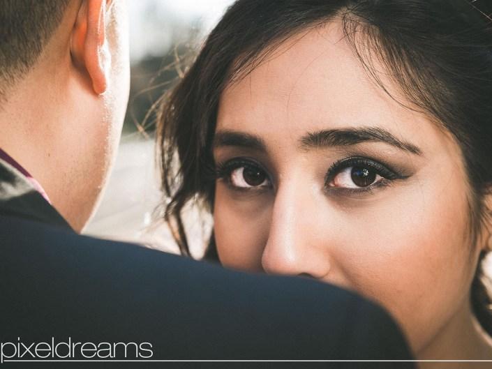 Braut posiert vor der Kamera an der Schulter des Bräutigam - perfektes Braut Make up und Brautfrisur - Hochzeitsfotos von Pixeldreams in Köln, Bonn, Düsseldorf, Bochum, Essen und deutschlandweit