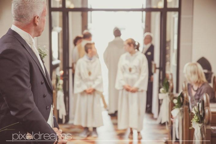 Bäutigam wartet auf seine Braut. Er sieht sie zum ersten mal im Brautkleid. Die Hochzeit/ Trauung findet in der St. Antonius Kirche in Swisttal statt. Hochzeitsfotograf Pixeldreams ist Deutschlandweit unterwegs.