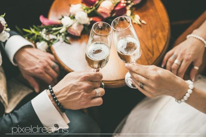 Braut und Bräutigam stoßen mit Sekt an. Hochzeitsfoto aus der Vogelperspektive. Trauringe und Brautstrauß.