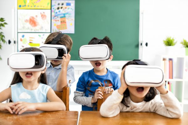 surprised students with virtual reality headset in classroom